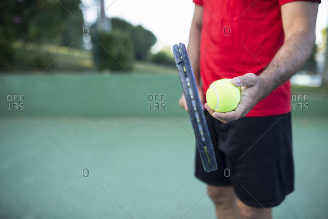 Unrecognizable sportsman holding ball and racquet while standing on tennis court