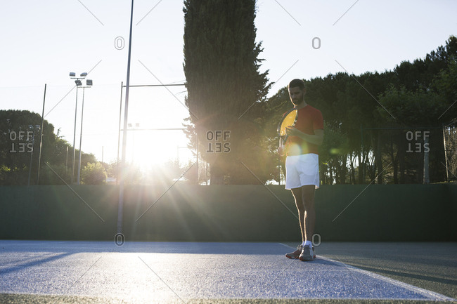 Handsome man holding racket and looking down while standing on tennis court