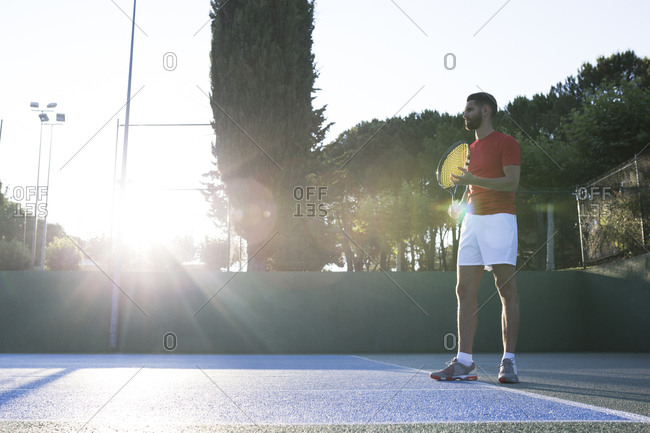 Handsome man holding racket and standing in ready position while playing tennis