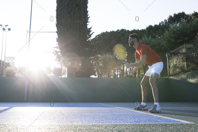 Man holding racket and standing in ready position while playing tennis