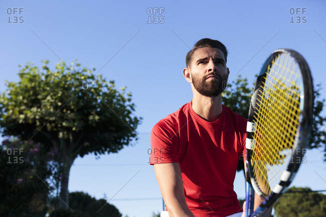 Handsome man holding racket while playing tennis on court