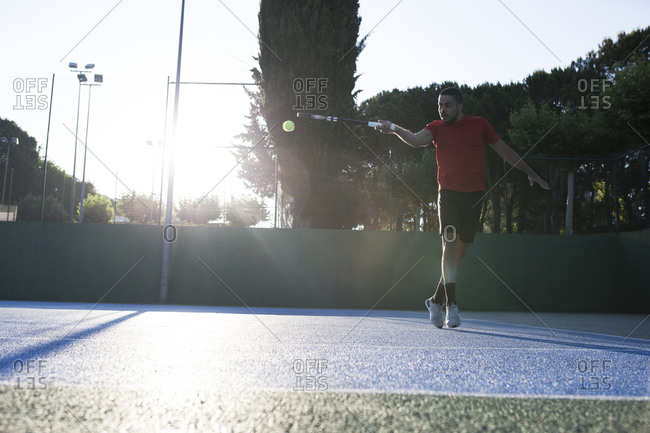 Handsome guy using racket to hit ball while playing tennis on court