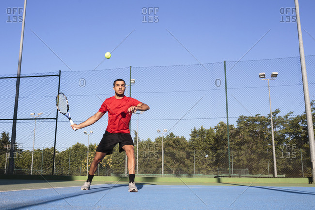 Handsome man on court preparing to hit ball while playing tennis