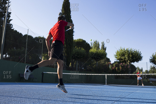 Man using racket to hit ball while playing tennis match