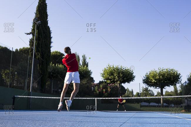 Man hitting ball while playing tennis on court