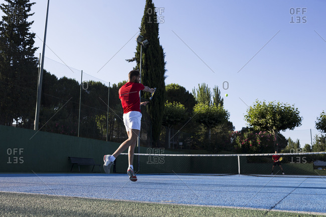 Man using racquet to hit ball while playing tennis