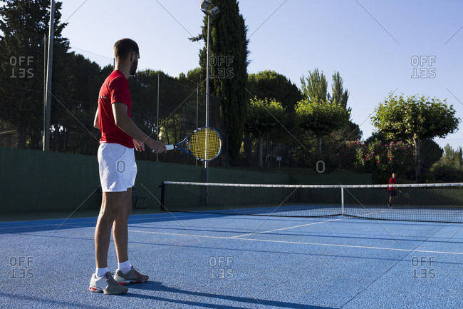 Man holding racket and standing in ready position while playing tennis match