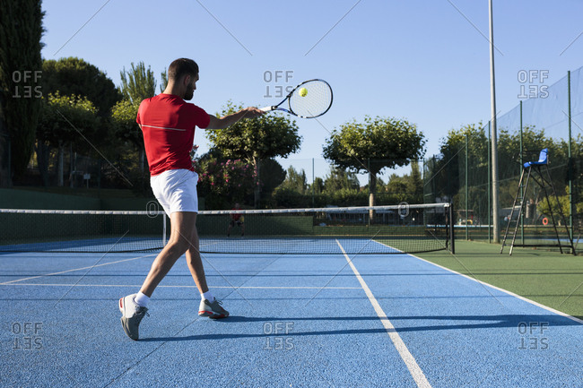 Rear view of man using racquet to hit ball while playing tennis