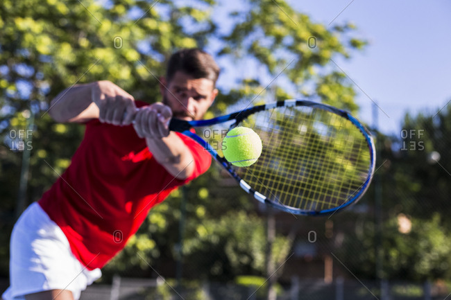 Blurred athlete holding racket and hitting ball while playing tennis