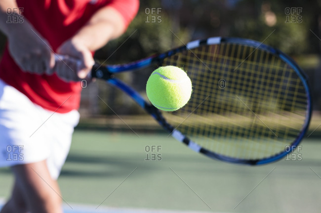 Unrecognizable blurred athlete holding racket and hitting ball while playing tennis