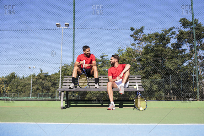 Two handsome guys with rackets sitting on bench and smiling on a tennis court