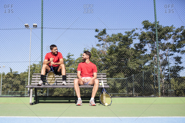 Two handsome men with rackets sitting on bench and smiling on a tennis court