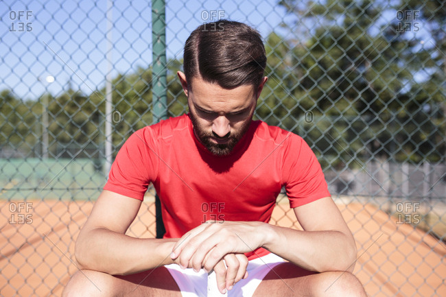 Handsome man with racket sitting on bench looking down on a tennis court