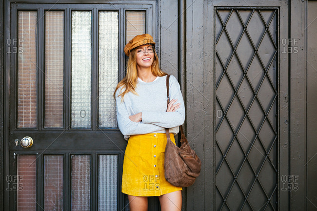 Smiling chic woman standing in front of a door on the street.