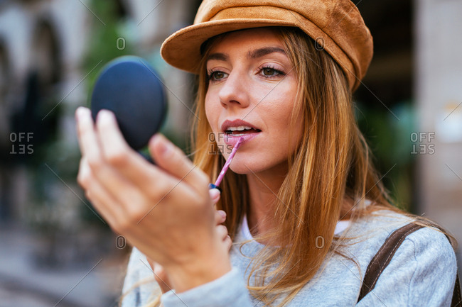 Chic woman wearing beret checking makeup on the street.