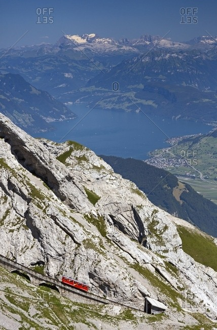 August 2, 2013: The red Cogwheel Railway going up Pilatus Mountain, in the background the Lucerna lake, Border Area between the Cantons of Lucerne, Nidwalden and Obwalden, Switzerland, Europe