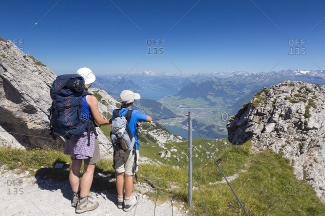 August 2, 2013: Hikers on the Pilatus mountain area, in the background the Lucerne lake, Border Area between the Cantons of Lucerne, Nidwalden and Obwalden, Switzerland, Europe