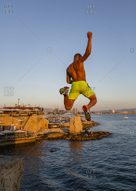 October 22, 2017: Man jumping to the water from the old city walls, Acre (Akko), Israel.