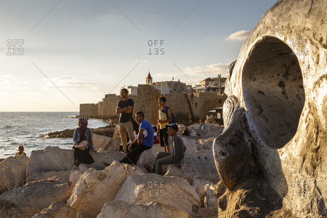 October 22, 2017: People sitting by the water in the old city, Acre (Akko), Israel.