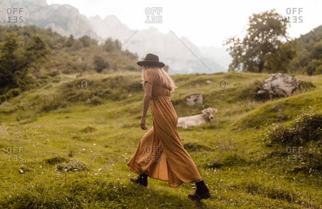 Woman with hat walking by meadow mountains background