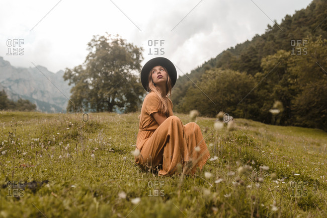 Woman with hat sitting on meadow mountains background