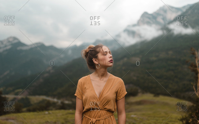 Portrait blonde woman resting on meadow in a cloudy day mountains background