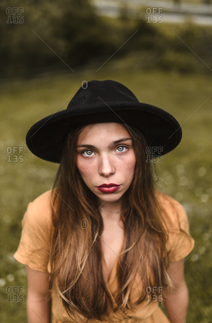 Portrait blonde woman of blue eyes and black hat looking at camera