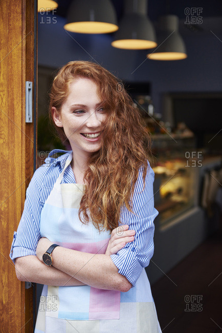 Happy young woman at the entrance of a bakery