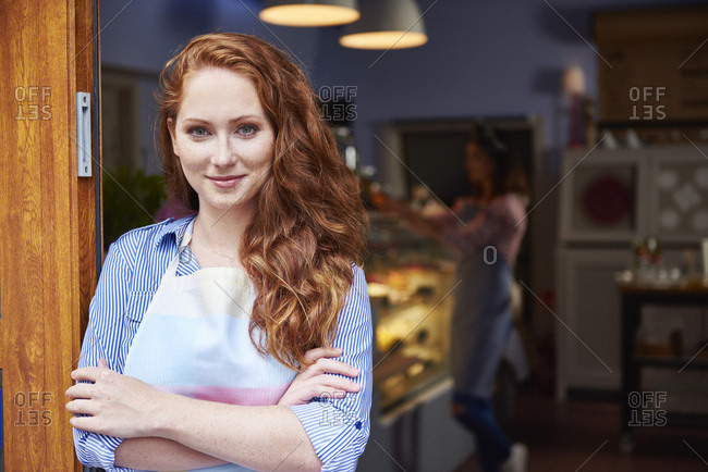 Portrait of smiling young woman at the entrance of a bakery