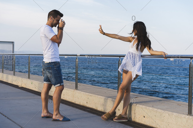 Young urban couple taking pictures by the sea- woman making peace sign