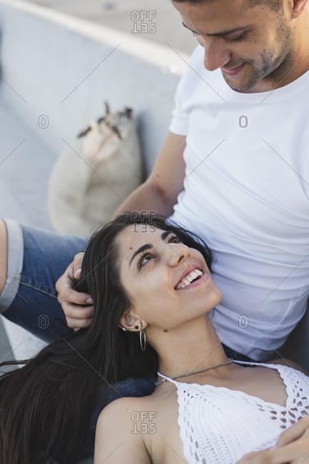 Happy young woman lying on lap of her boyfriend- portrait