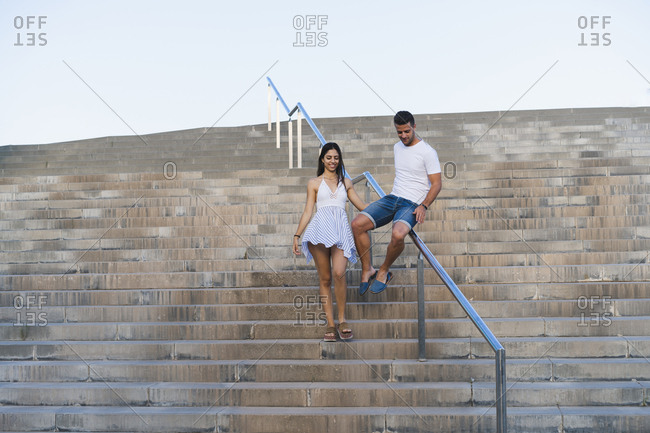 Young couple walking down stair- man sliding on railing