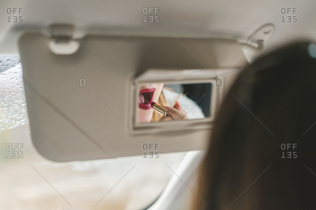 Woman mirrored in rear view mirror applying red lipstick in car