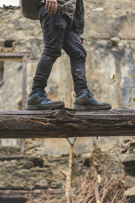 Man balancing on dead wood- partial view