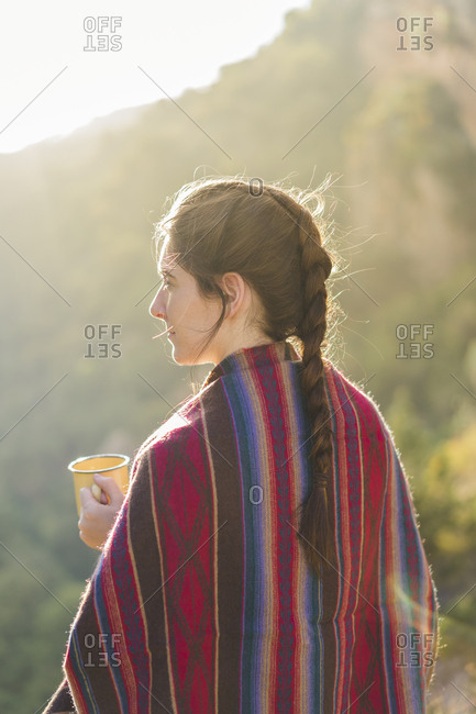 Spain- Alquezar- woman with braid and coffee mug at backlight