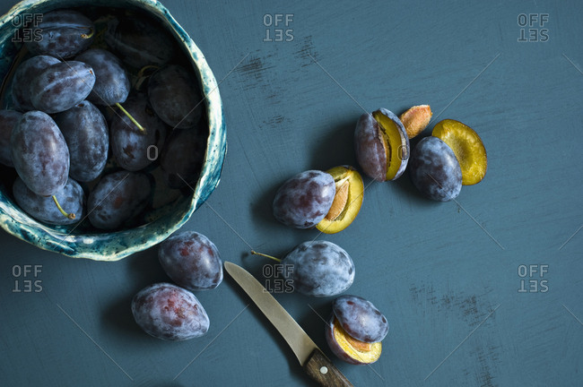 Sliced and whole plums and a kitchen knife