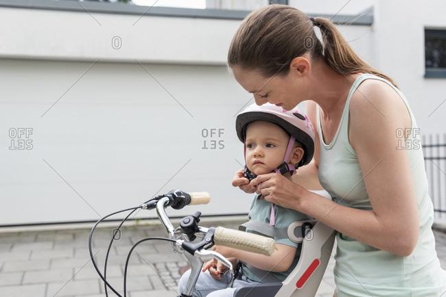 Mother and daughter- daughter wearing helmet sitting in children's seat