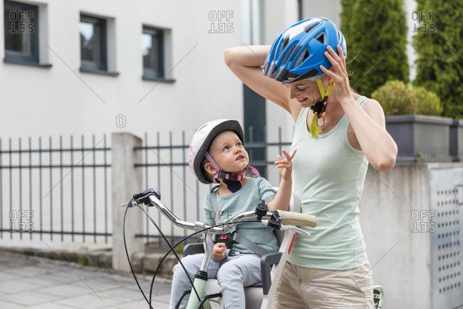 Mother and daughter wearing helmet- daughter sitting in children's seat