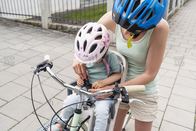 Mother and daughter riding bicycle- daughter wearing helmet sitting in children's seat- fastening seat belt