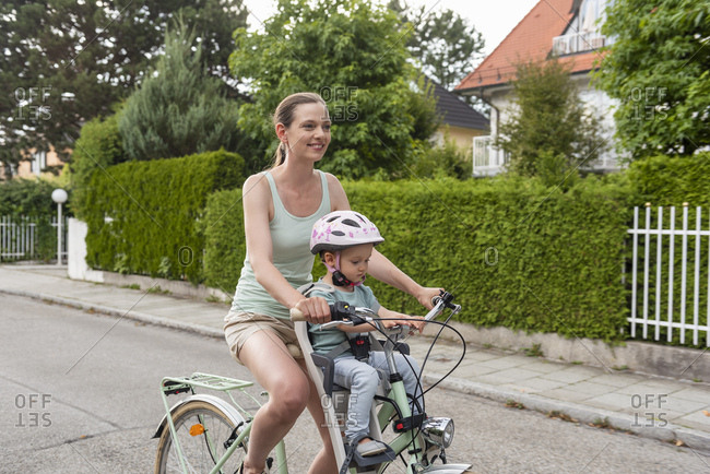 Mother and daughter riding bicycle- daughter wearing helmet sitting in children's seat