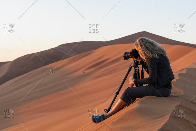 Africa- Namibia- Namib desert- Naukluft National Park- female photographer photographing at early morning light- sitting on sand dune