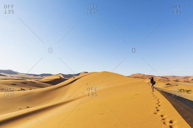 Africa- Namibia- Namib desert- Naukluft National Park- female tourist walking on dune