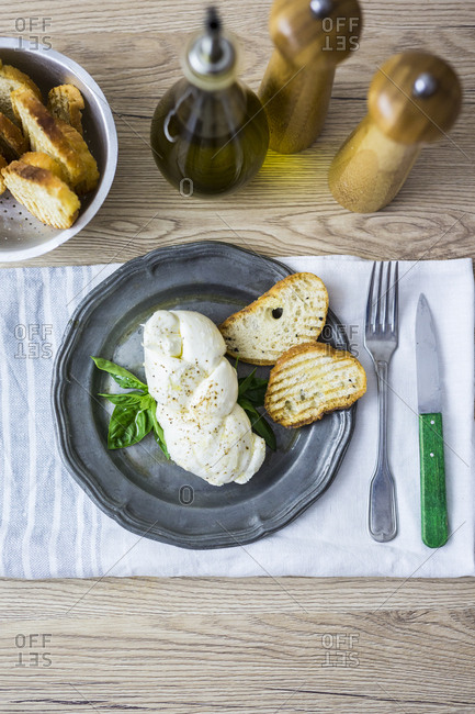 Mozzarella braid- basil and bread on plate