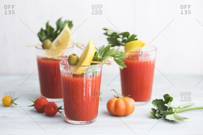 Glasses of fresh spicy tomato juice with celery garnished with lemon slice- green olive and parsley