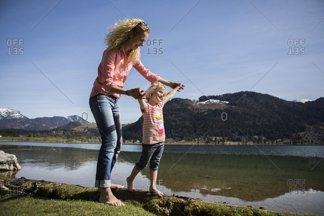 Austria- Tyrol- Walchsee- happy mother and daughter walking at the lake