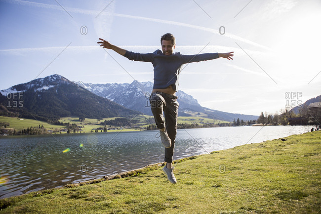 Austria- Tyrol- Walchsee- happy man jumping at the lake