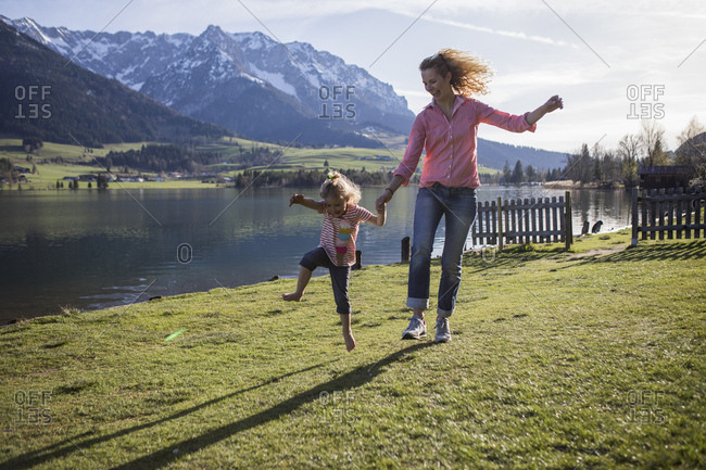 Austria- Tyrol- Walchsee- carefree mother and daughter jumping at the lake