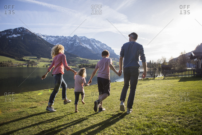 Austria- Tyrol- Walchsee- happy family walking at the lakeside