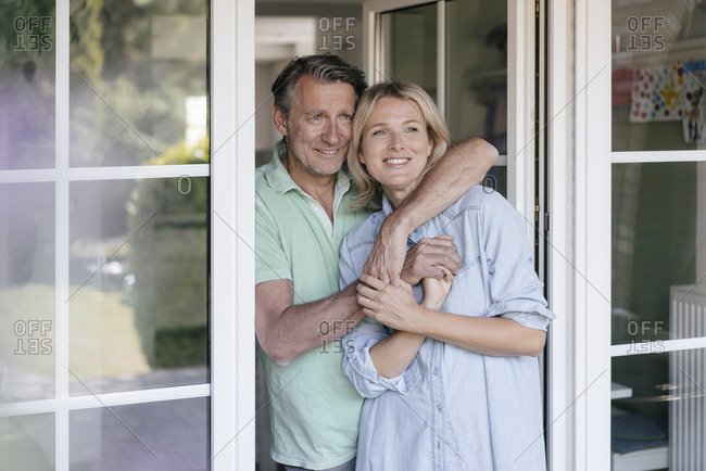 Happy mature couple hugging at French window