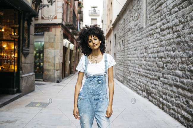 Spain- Barcelona- portrait of woman with curly hair wearing dungarees